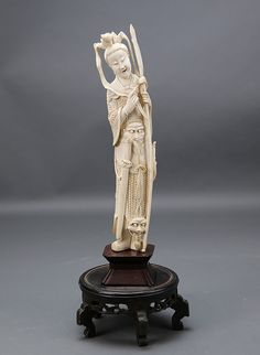 Chinese Carved Ivory Warrior Deity Qing Dynasty Early 19th century wearing armor and carrying a spear with a sword and a quiver of arrows at her waist. Adorned with three masks and a headdress.