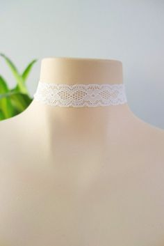 """This white choker features a stretchy lace band with gold hardware details and an adjustable chain and lobster clasp for closure. - Width .75"""" - Length: 12"""""""