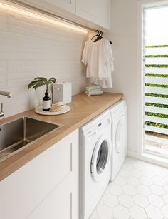 This stylish laundry will make you want to do the washing - - With its herringbone oak benchtop, white hexagon tiles and bagged-brick splashback, this laundry is anything but ordinary. Take a look here. Modern Laundry Rooms, Laundry Room Layouts, Laundry Room Remodel, Laundry Room Organization, Laundry In Bathroom, Laundry Closet, Laundry Cupboard, Laundry Cabinets, Laundry Room Small