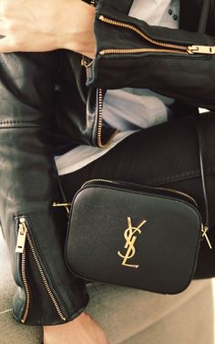 Via Just The Design: Camilla Pihl is wearing a black and gold Yves Saint Laurent clutch bag paired with a leather jacket and black skinny jeans