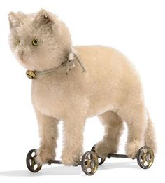 A STEIFF WHITE CAT ON WHEELS, (1317), standing, mohair, yellow and black glass eyes, pink stitching, whiskers, ribbon with bell, gold painted cast-metal wheels and FF button with remains of white tag, circa 1910 -- 7in. (18cm.) long | Private Collections & Country House Sales Auction | 20th Century, All other categories of objects | Christie's