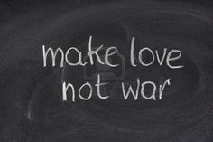 make love not war - anti-war slogan commonly associated with the American counterculture of the 1960sm white chalk handwriting on blackboard Stock Photo