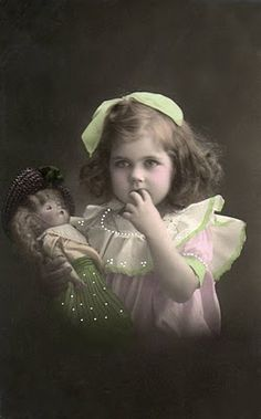 Vintage photo of beautiful little girl with her doll.