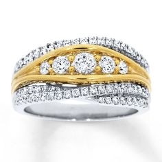 A tapered band of 14K yellow gold sparkles with round diamonds in the center of this intriguing anniversary band for her. Lines of round diamonds set in 14K white gold sweep above and below the center to complete the look, bringing the total diamond weight to 1 carat. Diamond Total Carat Weight may range from .95 - 1.11 carats.