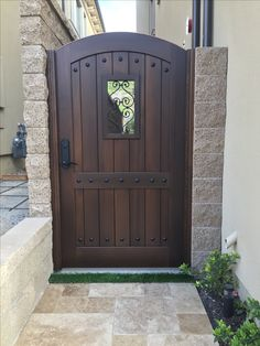 Custom Wood Gate by Garden Passages - Tuscan Style Arched Top With Large Rectangular Opening and Decorative Iron Grill with Decorative Clavos.