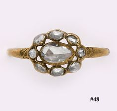 Cushion-cut diamond, silver and gold Georgian-period ring. Exquisite early 1800's engagement ring set with a center cushion cut diamond with a surround of small diamonds all set in silver with a yellow gold shank.  The ring sits very low to the finger and was designed for candle light.