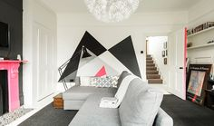 Gorgeous grey sofa, pink painted fireplace, mural painted wall.