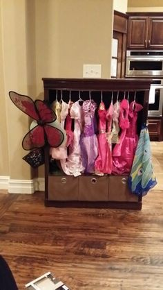 Dress - up organizer made out of old bookcase with shelves removed. Tension rod, basket, hooks, and canvas bins keep everything organized.