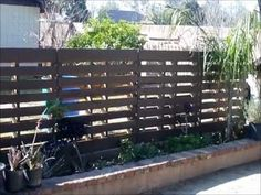 Pallet fence construction for side and/or front yard? Note flat tie plates and placement of metal stabilization bars. Also, dark paint ++ :)