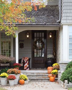 Visitors may never get past the porch when the space is this inviting! Mix plump pumpkins with several baskets of fall flowers in a display that weaves its way up the steps.