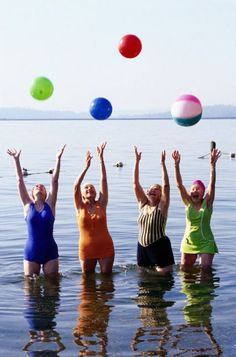 never too old to have fun! Four ladies in swim suits playing with beach balls