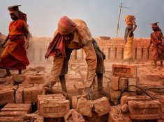 "Photograph by Shibasish Saha, National Geographic Your Shot  Laborers work among the dust and debris at a brick field in Kolkata, India. ""Men and women work together every day to earn some money for their family,"""