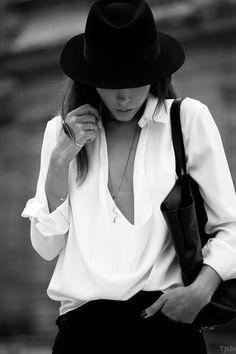 She's wearing a white long sleeved shirt with collar and deep plunge neckline. Sleeves slightly rolled. Black shoulder bag and black round mid brim hat. Long thin pendant. She is boss in every way. Style Planet
