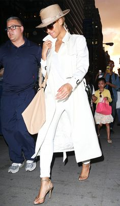 Beyoncé in an all white look with a camel fedora and strappy heels