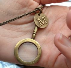 Found objects = wearable art:  Initial pendant, M, and a little old magnifying glass on a long bronze chain.