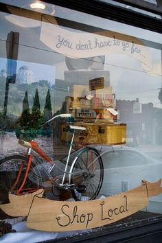 """you don't have to go far...Shop Local."" (clever window display)"
