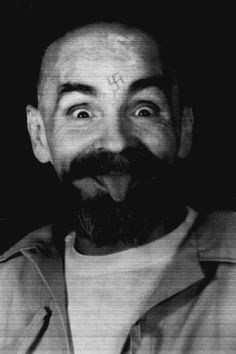 Charles Manson clowns around as he is led to his cell upon the conclusion of his exclusive interview with Reuters, August 25, 1989.