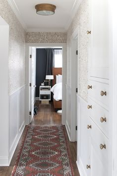 Tips & Tricks for Scoring Vintage Rugs Hallway with Wainscoting, Vintage Rug Runner, Built-In Linen Cabinet, Brass Light Fixture, and Floral Wallpaper Moulding And Millwork, Dark Accent Walls, Flur Design, Hallway Designs, Hallway Ideas, Entryway Ideas, Tadelakt, Hallway Decorating, Cottage