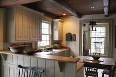 I like how the small table tucks into this kitchen and how the eye is drawn up from the cabinets to the wood ceiling