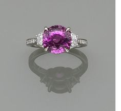 A pink sapphire and diamond ring, Paolo Costagli  centering a circular-cut pink sapphire weighing 5.59 carats, flanked by half-moon-shaped diamonds, completed by round brilliant-cut diamonds; signed PC, for Paolo Costagli; mounted in platinum