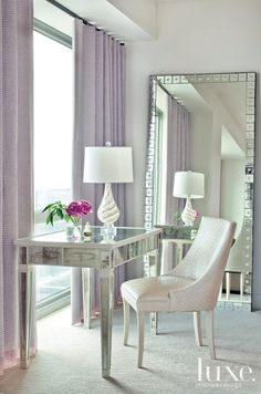This nook showcases a mirrored vanity paired with a Hunt chair by Suzanne Kasler for Hickory Chair. A vintage Murano glass lamp rests atop. The draperies, fabricated by Mountjoy Custom Draperies in Little Rock from Raoul Textiles, pick up the same lavender seen throughout the home.