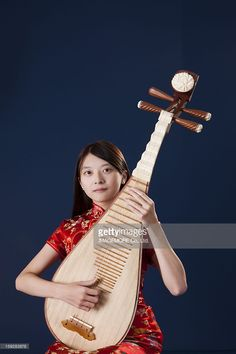 Stock-Foto : Young woman with cheongsam playing pipa and looking at the camera