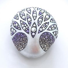 Tree of Life art stone, the stone is a lovely shape that fits perfectly in the palm of your hand. The pearly, silvery, white tree, branches out across the cold, wintery sky. Hundreds of dots have been meticulously painted in a vibrant array of lavender and white. The glossy branches and trunk of the tree has been accentuated with several coats of a glossy varnish. The lavender background has been finished with a matte varnish. The finished stone is art for your eyes, inspiration for your…