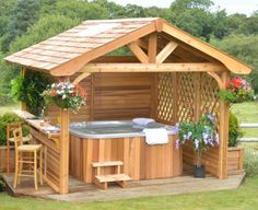 Wooden gazebo for hot tub with seating in the garden