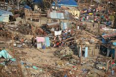 This aerial shot shows destroyed houses and residents waving a white flag on Victory Island off of the town of Guiuan in Eastern Samar provi...