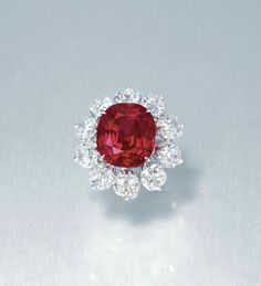 'THE CRIMSON FLAME RUBY'. AN EXTRAORDINARY RUBY AND DIAMOND RING. Set with a cushion-shaped ruby, weighing approximately 15.04 carats, within a cushion-shaped diamond surround, to the pavé-set circular-cut diamond three quarter-hoop, mounted in gold, ring size 5½. Price Realized $18,382,385 // Estimate $10,111,608 - $15,556,320. SSEF / GÜBELIN / Burma (Myanmar) origin / no indications of heating / 'pigeon blood red' [C. 1 December 2015 - HK] #Ruby