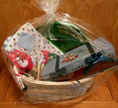 Kitchen basket includes towels, spatulas, measuring spoons, set of green chargers, and gift box for cookies or treats.