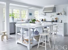 The kitchen island and countertops are topped with Carrara marble; the backsplash tiles are from Southampton Gallery of Marble and Tile. The faucet is from Kohler.