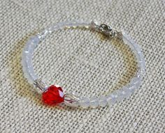 Swarovski Crystal Passions Red Heart Bling Memory Wire Bracelet $14.00 This beautiful bracelet is made with milky clear 6 mm and 8 mm faceted crystal rondelles, silver plated filigree spacers and a red faceted Swarovski Crystal Passions heart focal on stainless steel memory wire with a stainless steel lobster clasp closure.  This bracelet can be adjusted to any size...