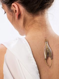 "The 'e-pulse conductor' is a pendant without a chain, harvesting bioelectricity from the human body's neurological system, ""plugged"" into the spine via pincer interface."