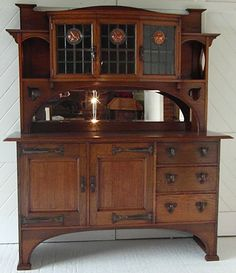 Arts & Crafts oak dresser with 3 leaded glass panels incorporating stylised copper roundels and cut out decoration.  Waring & Gillow (stamped drawer)  Circa 1900
