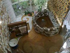 Cuarto de baño, pared de botellas y troncos, tina con piedras