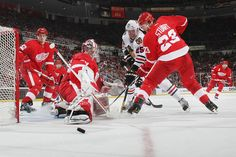 APRIL 07: Jimmy Howard #35 of the Detroit Red Wings makes a pad save while teammates Brad Stuart #23 and Jonathan Ericsson #52 defend Viktor Stalberg #25 of the Chicago Blackhawks during an NHL game at Joe Louis Arena on April 7, 2012 in Detroit, Michigan. (Photo by Dave Reginek/NHLI via Getty Images)