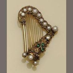 A Victorian gold, pearl and emerald brooch in the form of a harp and a shamrock, both symbols of Ireland. (Bonhams)