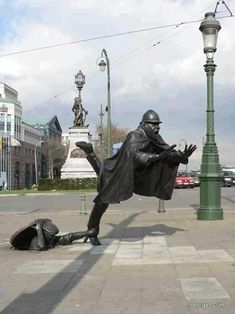 Amazing balance in this statue!  Man, manhole, caped man, foot caught, statue, art