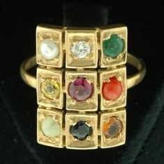 """18K gold navarathna* """"9 gem"""" ring from India. This beautiful piece is studded with hessonite garnet, emerald, ruby, exotic pearl, diamond, red coral, sapphire and cat's eye.    Meaning of Navarathna:  Navarathna, literally a Sanskrit compound word meaning """"nine gems"""", is a talisman or accessory set with nine gems. It is a popular item for celebrities and tourists in India and can be found at the finest jewelry stores and lowly gift shops. Essentially navarathna* is a jeweled yantra or ..."""