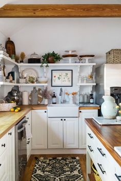 new england farmhouse kitchen island with organized shelving and wood counter tops