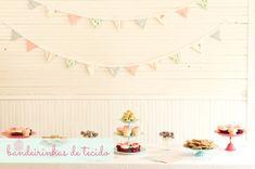 A mesa dos doces e do bolo é a queridinha de toda e qualquer festa.Sempre que vamos idealizá-la surge a dúvida sobre qual a melhor decoração de pano de fundo usar.Balões, pompons de papel ou bandeirinhas de tecido? Bastidores ou cortinas de fitas...