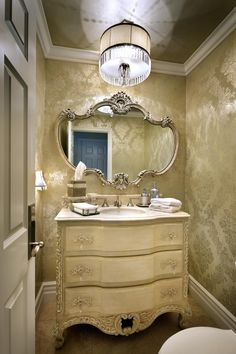 An easy and inexpensive update to this powder room included changing the faucet from brass to satin nickel; adding a luxurious brocade wallpaper with a metallic ceiling; removing the dome ceiling light fixture to make way for a spectacular crystal and linen chandelier; replacing the crackle effect on the vanity cabinet with a metallic wash and Modulo stencils; and eliminating the antique brass vanity hardware in favor of lovely satin nickel and crystal pulls. Photo by Anthony Gomez.