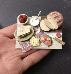 Dolls house miniature making sandwiches set for 12th scale dolls house. Made from polymer clay, this dear little set will complete a lived-in kitchen! All items are safely fixed onto the wood board. The board measures 4.8 cm x 6.5 cm. Set includes everything in photos, including bread, knife, tomatoes, mayonnaise, ham and much more! Perfect, realistic addition to any dolls house kitchen! I can make custom orders, please message me :) Thanks for looking! Lauren