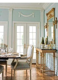 Blue walls, pretty and pale, add to the traditional French style of this dining room with Louis XVI style marble-topped console table and gilt mirror.