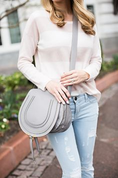 Emily Jackson of The Ivory Lane pairs our striped Eloisa Sweater with a neutral handbag and destroyed denim.