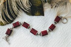 Vintage Mexico Minimalist Sterling Silver Red Jasper Inlay Bracelet  The beautiful inlaid, crimson jasper is streaked with a touch of black matrix. The stones are polished and pop with color against the shine of the silver. They actually appear to wrap around.  The seven link bracelet is 7 1/4 inches long by approximately 1/2 inch wide. Nice toggle closure.  Marked MEXICO 925. The total weight is 39 grams. Excellent condition. Circa 1980s.