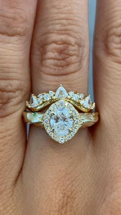 Blanca and Tempest create a stunning vintage inspired yellow gold wedding ring set with intricate details. Blanca features a unique handcrafted and hand engraved sculptural band dotted with emerald, ruby, and sapphire accent stones. At her heart she has a brilliant oval diamond surrounded by a diamond halo. Tempest is a contoured band set with a collection of trillion and round diamond stones. See these two in more detail on our website! #kenanddanadesign #customdesign #nycjeweler… Wedding Rings Sets Gold, Diamond Wedding Bands, Gold Wedding, Wedding Jewelry, Gold Jewelry, Vintage Jewelry, Stacked Engagement Ring, Vintage Inspired Engagement Rings, Gemstone Engagement Rings