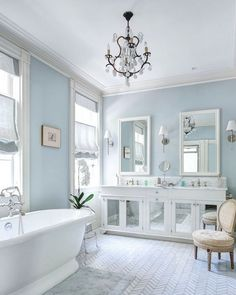 Master Bathroom:blue walls,chevron marble tile,blue bath rug,freestanding.pedestal bathtub,tub faucet with hand shower,French vanity chair,oval back vanity chair, white built in vanity with mirrored doors,marble counters, built in dual sink vanity,nickel cabinet pulls.