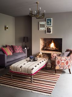 Upholstering furniture, such as the ottoman and armchair here, in fabrics inspired by the textural qualities and motifs of kilim rugs works well in a layered scheme. Homes & Gardens. Styling Claudia Bryant, photograph Paul Raeside. http://www.hglivingbeautifully.com/2016/01/07/clever-design-ideas-decorating-with-rugs/